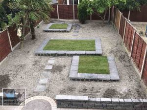 Landscape area with gravel and raised lawn beds